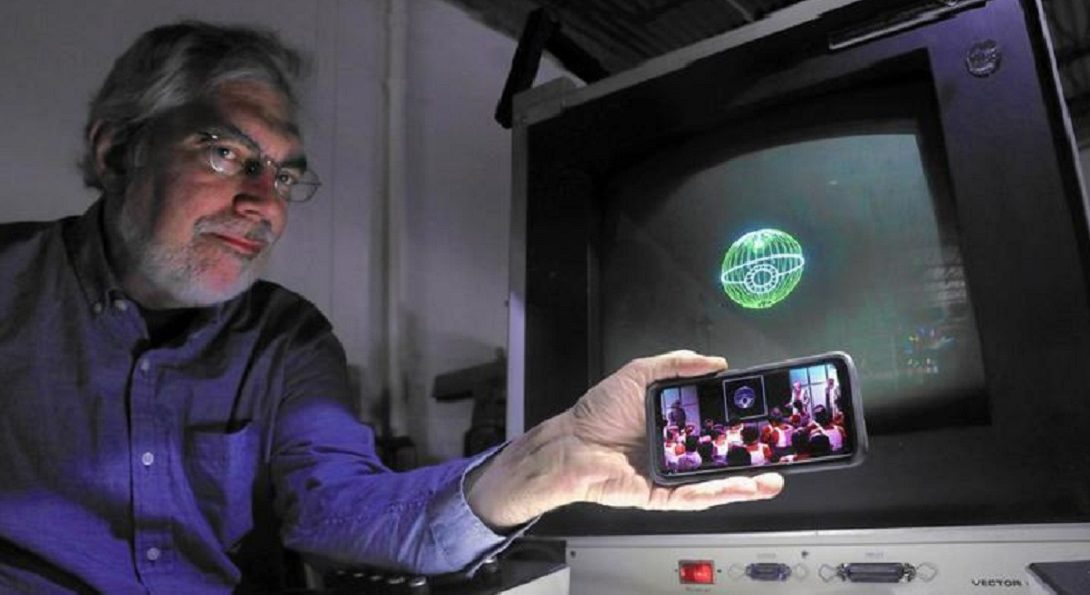 "Aura Technologies President Steve Heminover holds a phone with a scene from the original ""Star Wars"" beside an image of the Death Star on the computer that was used to create digital effects for a small part of the 1977 film. Heminover was a student at the UIC lab where the effects were created. (Chris Sweda/Chicago Tribune)"