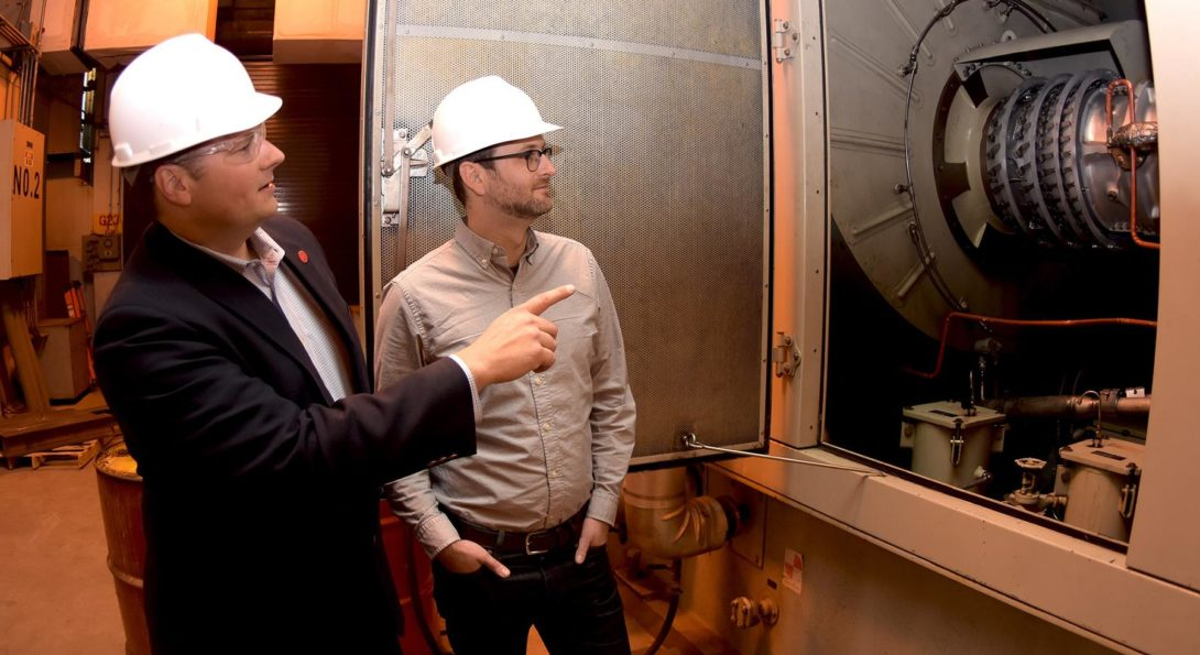 Cliff Haefke, director of the UIC Energy Resources Center, left, and policy analyst Graeme Miller analyze the 7-megawatt combined heat and power combustion turbine at the UIC West Campus Utilities Plant.