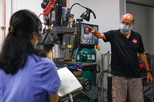 Two people wearing masks in a machine shop classroom